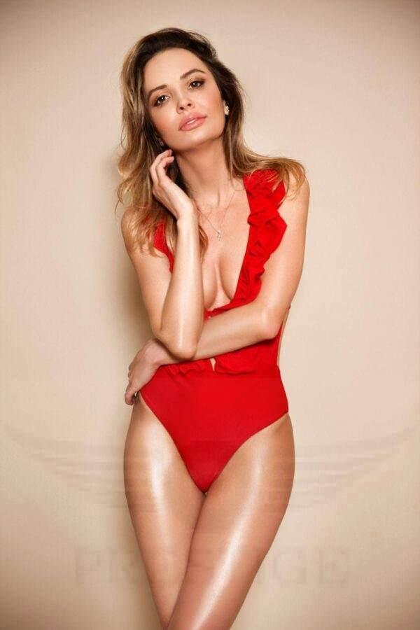 Sexy blonde escort Connie in a hot red bodysuit